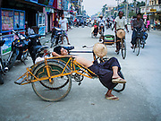 10 NOVEMBER 2014 - SITTWE, MYANMAR: A rickshaw taxi driver naps in the evening  in Sittwe, Myanmar. Most of the taxis in Sittwe are still pedal bike rickshaws. Most neighborhoods in Sittwe rely on well water. Sittwe is a small town in the Myanmar state of Rakhine, on the Bay of Bengal.    PHOTO BY JACK KURTZ