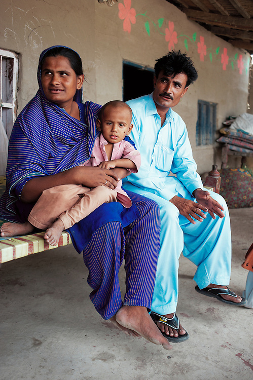 Najma Shafi, 30 years old with her child Shariaz, 45 months old and husband Shafi Muhammad in the village of Sheer Ali Shah, Thatta, Sindh, Pakistan on July 1, 2011. Shariaz developed asthma and is now recovering.