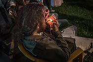 Foreign man lights a &quot;spliff&quot;, or marijuana cigarette, at a live reggae concert at the Twelve Tribes of Israel headquarters.  Shashemene, Ethiopia.  Ganja (marijuana) is considered sacred to Rastafarians.  They believe it cleans the body, mind and soul.  &quot;Ganja&quot; is derived from the Sanskrit word, &quot;ganjika&quot; the name uesd in ancient India and Nepal for marijuana.  Many believe that ganja sacrament was introduced to post-abolition Jamaica by Indian migrants brought in by the British.  <br /> <br /> Ganja was imported by Arab traders, who called it &quot;dagga&quot;, to Central and Southern Africa in the 8th century.  Rastas claim it is another aspect of them reclaiming their African cultural identity.