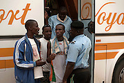 Nigerien policemen and young african migrants just arriving by bus in Agadez city. The migrants are forced to pay atleast 10 000 CFA to policemen to be able to enter the city.