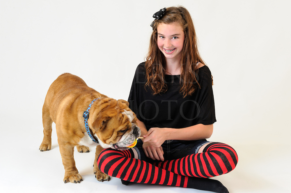 Young girl with a dog licking her lollipop, a thirteen year old teenager in striped knee socks and her pet bulldog.