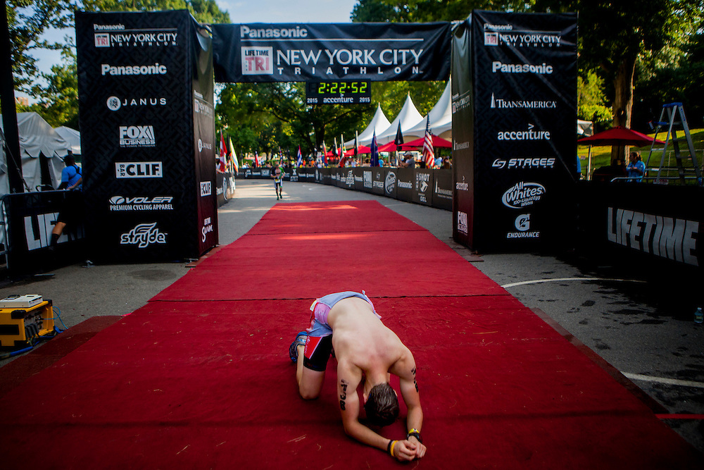 NEW YORK, N.Y. - JULY 19, 2015: A triathlete falls to his knees after completing the 15th Annual Panasonic New York City Triathlon. CREDIT: Sam Hodgson for The New York Times