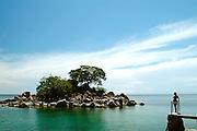 Kaya Mawa* Lodge.  A lady looks over to honeymoon island in the clear waters of Lake Malawi.*Chicewa language for 'Maybe tomorrow'. Likoma Island, Lake Malawi.
