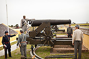 Confederate re-enactors man a giant Civil War canon in Fort Moultrie aimed at Fort Sumter in Charleston Harbor Charleston, SC. The re-enactors are part of the 150th commemoration of the US Civil War.