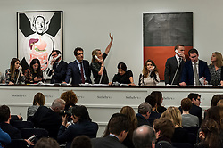 "© Licensed to London News Pictures. 10/02/2016. London, UK.  Sotheby's sales staff make bids on behalf of telephone clients standing in front of (L to R) Mike Kelly's ""Visceral Egg"" and Günther Förg's ""Untitled"", which sold for a hammer price of £0.2m and £0.32m respectively, at Sotheby's Contemporary Art evening sale in New Bond Street.   Photo credit : Stephen Chung/LNP"