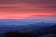 View of the Brendon Hills from Cothelstone Hill on the Quantocks, during a sunset. The mist gives a muted appearance and has blended with the long exposure to give the violet colouration in the hills.