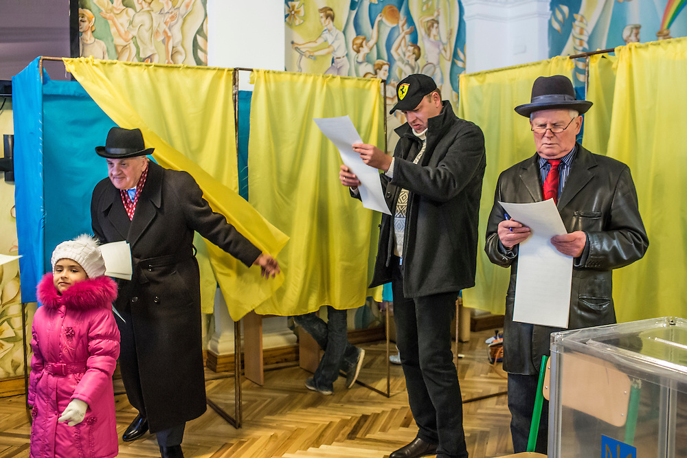 KIEV, UKRAINE - OCTOBER 26: Voters review their ballots before casting their votes in parliamentary elections at a polling station on October 26, 2014 in Kiev, Ukraine. Although a low turnout is expected in the east of the country amid continued fighting between Ukrainian forces and pro-Russian separatists, Ukraine is expected to elect a pro-Western parliament in a further move away from Russian influence. (Photo by Brendan Hoffman/Getty Images) *** Local Caption ***