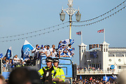 The open top bus makes its way through the crowds and passes by Brighton Pier during the Brighton & Hove Albion Football Club Promotion Parade at Brighton Seafront, Brighton, East Sussex. United Kingdom on 14 May 2017. Photo by Ellie Hoad.
