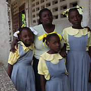 Marie Nicole with her daughters: Clara (5), Rachelle (8) and Paul Monica (12) outside the Pyramid shool in Leogane. Marie Nicole is part of a parents association at the school. ..The Pyramid School in Leogane was damaged during the earthquake. CARE has been supporting the school as part of the Education Project which includes developent of parents associations and class committees. They have also donated benches, desks, tables, and chairs. In addition CARE has built 9 latrines, as well as a renovated hand washing station. The WASH team has also provided hygiene training with activities reaching a total of 135 students.