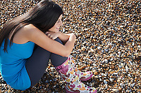 Young woman sitting on beach side view side view