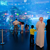United Arab Emirates, Dubai, Arab family in traditional clothing (Dishdasha for men, Abaya for women) visit Dubai Aquarium at Dubai Mall