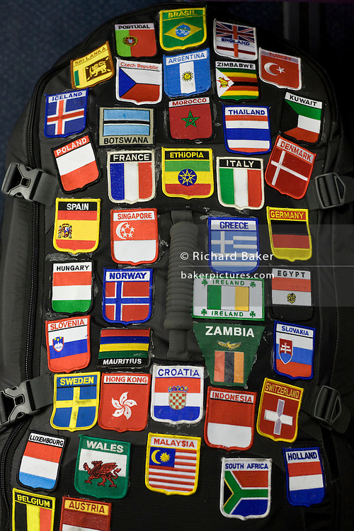"An accumulation of badges show where a passenger on board a Heathrow Express train to Heathrow Airport has travelled to. Sewn onto the traveller's rucksack, the countries represented by these patches show a much-travelled young person who has amassed a collection of world air miles and travel experiences, with their national flags and emblems on display in a way that adventurers show their routes and wanderlust to others, perhaps as proof of a lifetime wandering the world's borders and airports. As each badge is added, it accounts for new travel companions and the hazards and joys of modern air travel. From writer Alain de Botton's book project ""A Week at the Airport: A Heathrow Diary"" (2009)."