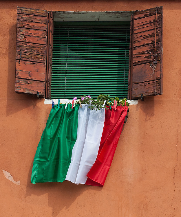 VENICE, ITALY - SEPTEMBER 18:  Italian flag is seen on the famous window of Lucia Massarotto which has become the symbol of protest against Lega Nord separatist and racist ideology on September 18, 2011 in Venice, Italy. The Northern League rally is held to call for the independence of Northern Italy, during which the leader of Lega Nord pours water from the River Po in the north of Italy into the Venetian Lagoon as a symbolic rite known as Rito dell'ampolla.