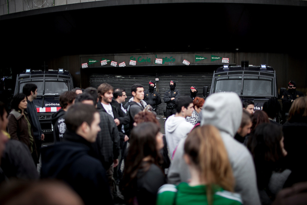 14-11-2012 Barcelona, Spain - Police guard a famous Spanish commercial center while people demonstrate during the European-wide 24h general strike against austerity called by the European Trades Union Congress.