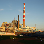 The Bridgeport Harbor Power Station provides a back drop to the ballpark during the Bridgeport Bluefish V Southern Maryland Blue Crabs, Atlantic League, Minor League ballgame at Harbor Yard Ballpark, Bridgeport, Connecticut, USA. Photo Tim Clayton