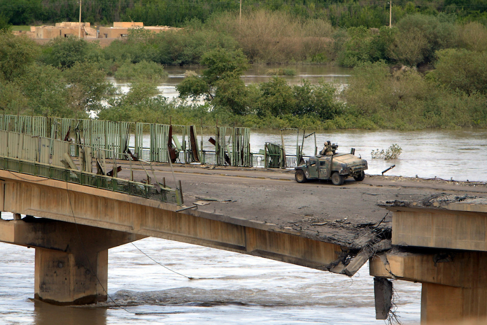 A US Marines Humvee rolls across a bridge over the Tigris River in Tikrit that was heavily damaged. THIS WAS ONE OF THE AREAS SECURED BY THE MARINES TODAY IN TIKRIT.  Marines moved into the region with little resistance.