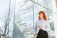Businesswoman holding laptop by glass wall in office