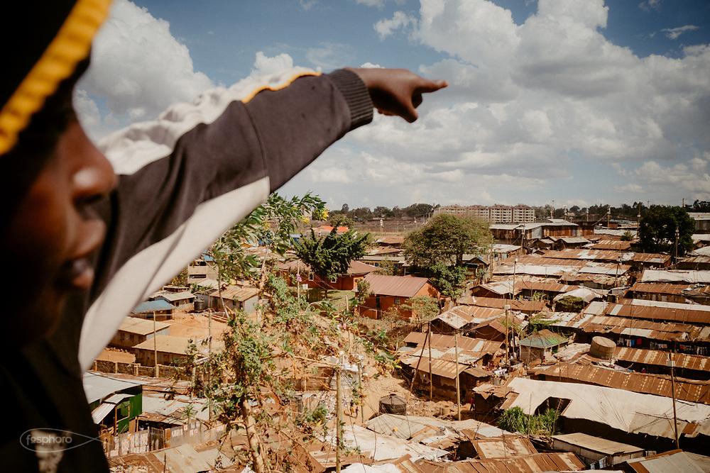 """Kenia 2017: Duncan, un ospite di """"Mdugu Ndogo"""" (centro di primo intervento per il recupero dei ragazzi di strada), indica la propria casa d'all'altro di Kibera"""