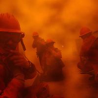 "Firefighters take cover behind a wall during the ""Old Fire"" in San Bernardino, Calif. Saturday, Oct. 25th 2003"