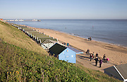 People walking on the seafront promenade on a sunny winter day, Southwold, Suffolk, England