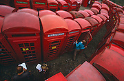 Looking down from a high viewpoint, prospective auction bidders take notes from their catalogues of old red British Telecom (BT) pay phone boxes which are lined up on display in their hundreds before the actual sale starts. The 'lots' are squeezed together along pathways allowing customers to thoroughly inspect their potential purchases' details. This is a wide-angle picture taken on the slant with the distant boxes curling around to the left. One man in blue who has opened the stiff-opening door, cranes his neck to look up into the ceiling of these solid cast-iron frames. The K-series kiosks were largely designed in 1936 by the iconic designer Giles Gilbert Scott.