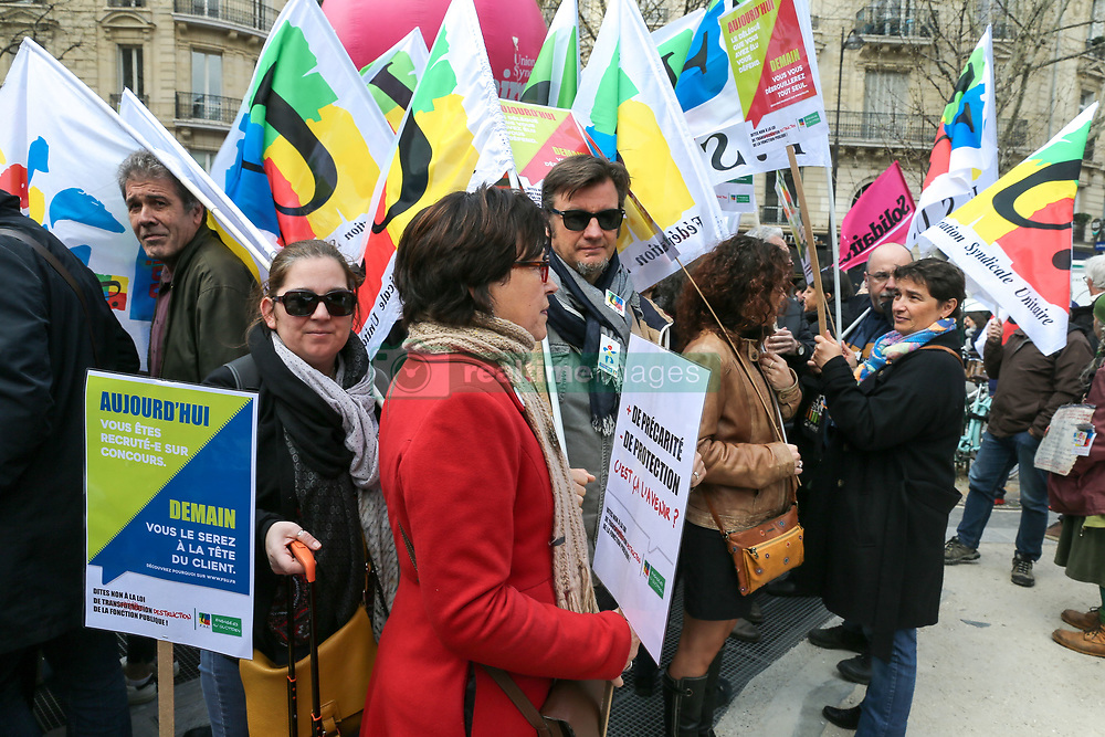 """March 27, 2019 - Paris, Ile-de-France, France - A woman holds a placard reading Â« more precariousness, less protection » during a demonstration at the call of several civil servants' workers' unions including the CGT, FSU, UNSA CFTC on March 27, 2019 in Paris to protest a bill to reform the public service sector. President Emmanuel Macron's government has launched what it called a """"profound modernisation"""" of France's 5.5m-strong civil service, a cost-cutting reform that envisages the loss of 120,000 jobs over the next three years. (Credit Image: © Michel Stoupak/NurPhoto via ZUMA Press)"""