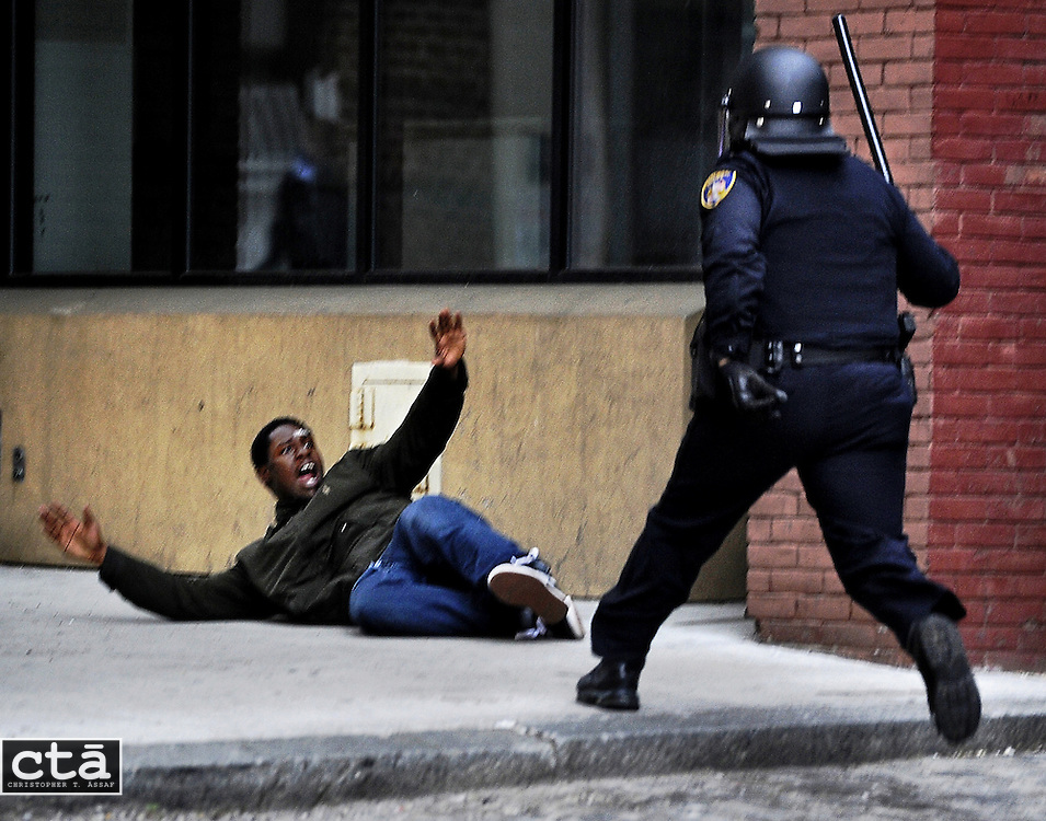 "A man screams ""Hands up!"" after being chased by a police officer in downtown Baltimore near Lexington Market. The man, who police suspected of looting and property damage, was running from police before he fell and was arrested. The looting and unrest April 27, 2015, followed the burial of Freddie Gray, who died while in police custody. Six officers were indicted in the cases brought by Baltimore State's Attorney Marilyn Mosby."