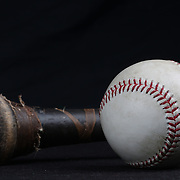 An authentic Rawlings used baseball from the 2012 Major League Baseball season showing the red stitching and markings next to a bat handle. 16th May 2012. Photo Tim Clayton