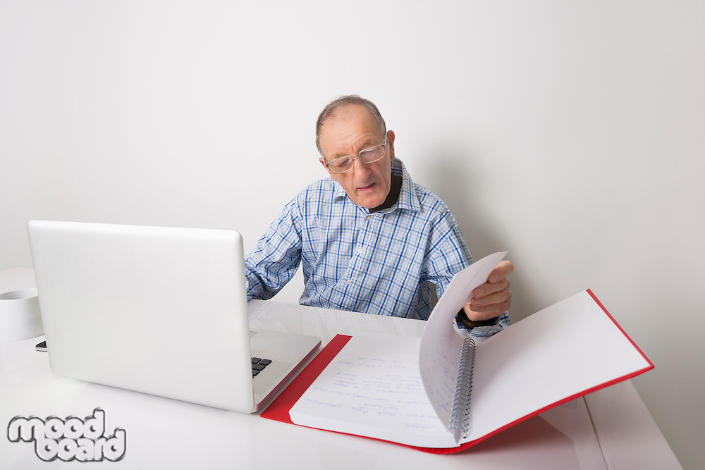 Senior businessman using laptop while reading file at office desk