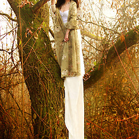 A brunette in a long white gown standing on a tree in an autumnal forest.
