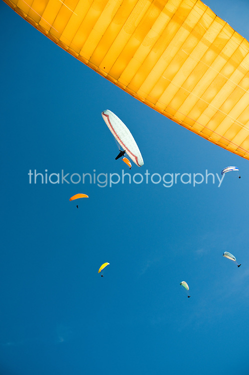 Graffic image looking up while paragliding - other paragliders almost in formation in thermal. Valle de Bravo, Mexico.