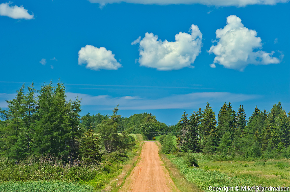 Country road, clouds and red soil<br />Annandale<br />Prince Edward Island<br />Canada