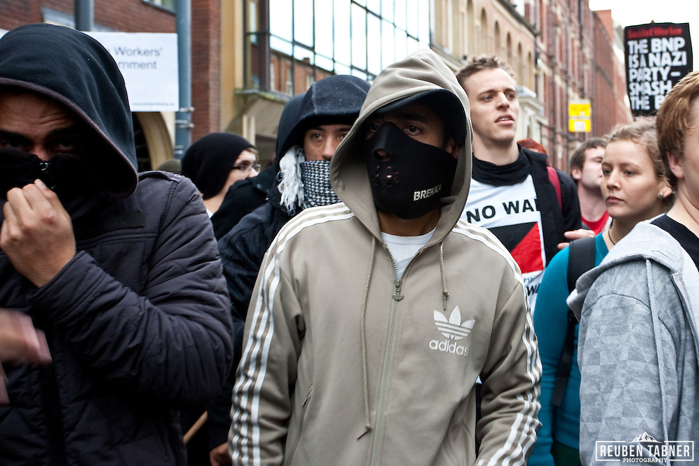 Masked youths attempt to break police lines to confront members of the English Defence League (EDL).