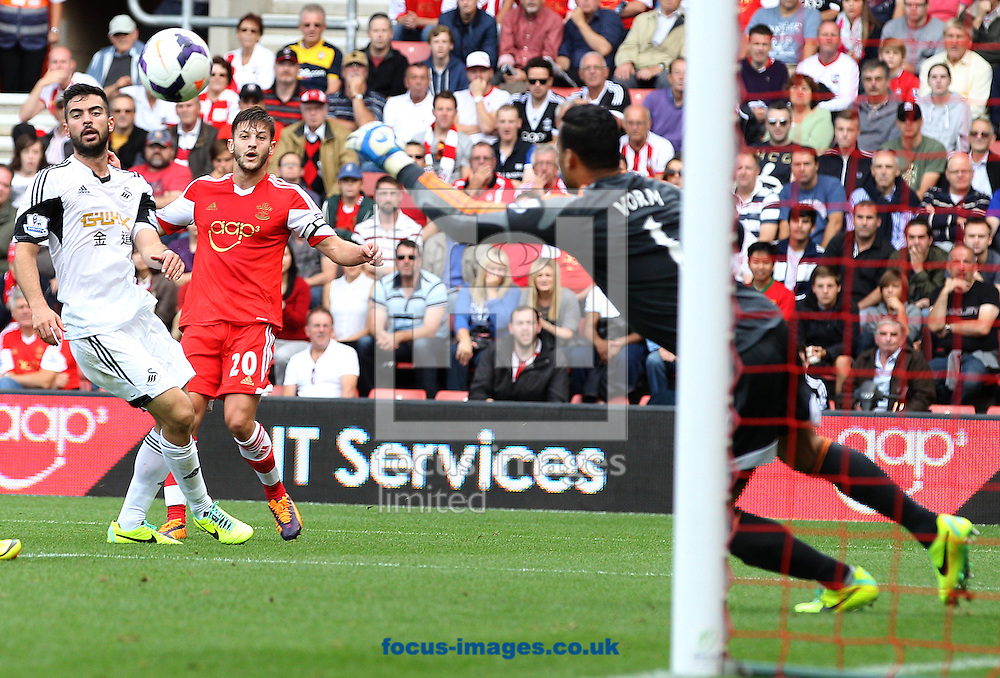 Picture by Paul Terry/Focus Images Ltd +44 7545 642257<br /> 06/10/2013<br /> Adam Lallana ( C)  of Southampton watches his shot go wide of the goal and of the Swansea City goalkeeper Michel Vorm ( R ) during the Barclays Premier League match at the St Mary's Stadium, Southampton.
