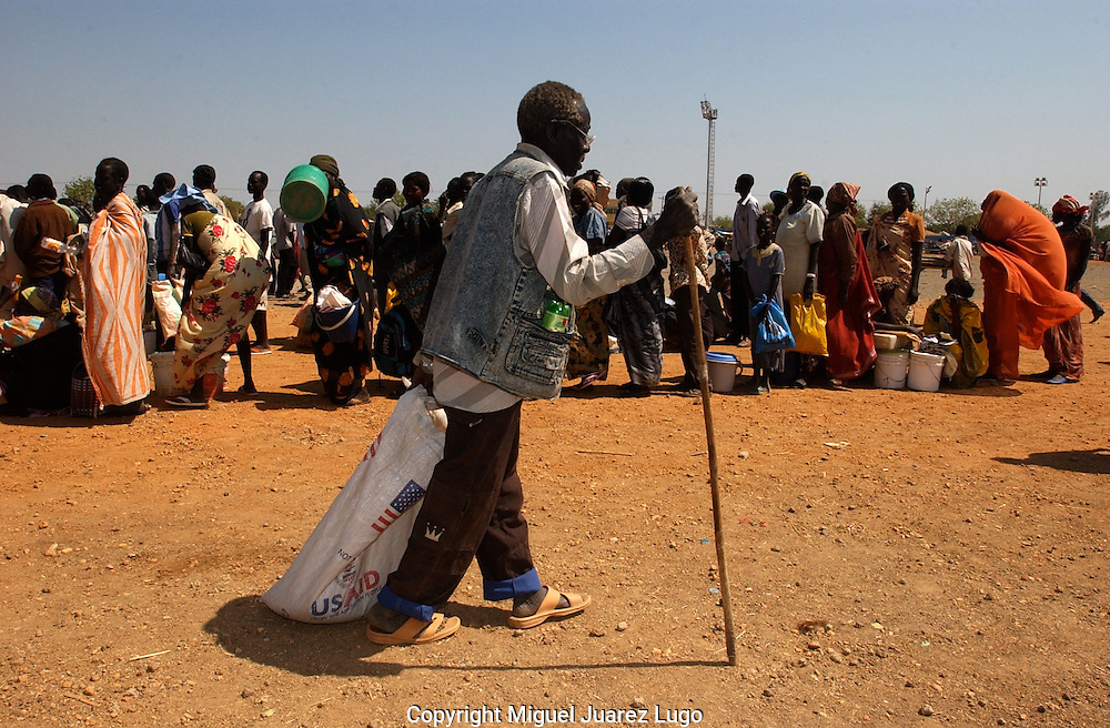 """After a 45 years life in Khartoum, 67 year old, Samuel Adiyang, arrived 15 days ago to this city of Malakal in South Sudan.  Like many others, Adiyang, drags his sack with a four kilos of american donated sorghum, a ration soppose to last one month for him and his other 5 members family. """"i am home, a just need a place to settle and die as i never want to return to the north"""" he said. (PHOTO: MIGUEL JUAREZ)."""