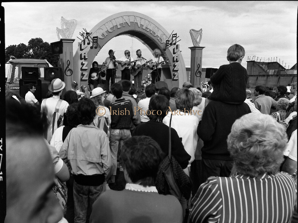 """Guinness Family Day At The Iveagh Gardens. (R83)..1988..02.07.1988..07.02.1988..2nd  July 1988..The family fun day for Guinness employees and their families took place at the Iveagh Gardens today. Top at the bill at the event were """"The Dubliners"""" who treated the crowd to a performance of all their hits. Ireland's penalty hero from Euro 88, Packie Bonner, was on hand to sign autographs for the fans...Image shows the Dubliners on stage entertaining all the families who turned out for the Guinness Family Fun Day at Iveagh Gardens."""