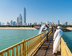 Skyline of modern office towers in downtown CBD from public pier with men fishing  in Kuwait City in Kuwait