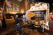 Boston, MA 12/08/2011.Occupy Boston members fill a waiting garbage truck as the city of Boston's deadline to vacate Dewey Square draws near on Thursday evening..Alex Jones / www.alexjonesphoto.com