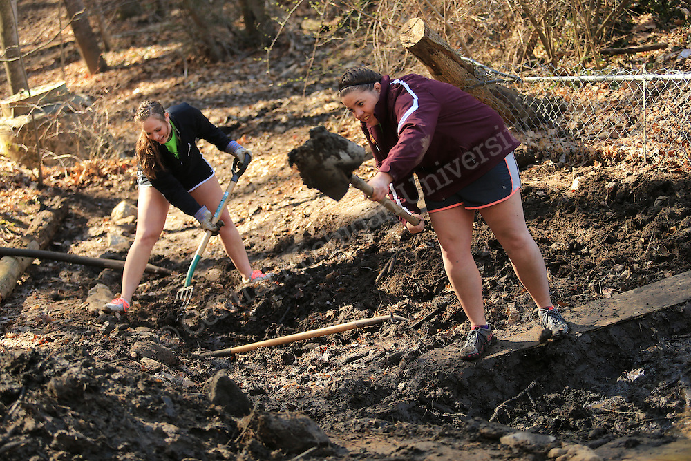 (left to right) Ally Vasilauskas, of Holland, and Jalisa Gorby, of Coldwater, help clear a stream bed of muck and debris on their Alternative Break. They were among nine CMU students who travelled to the YMCA of Western NC Youth Service Center to spend the week to help with projects to improve the center and in the community. They addressed access to sports and recreation and built a kiosk, cleared a stream bed and worked with elementary students in an after school program as their Alternative Break project. CMU is ranked fourth in the nation for the number of students participating in Alternative Breaks and fifth in the country for the most trips coordinated by a university. The program organizes about 40 trips each year with more than 400 students participating. Photo by Steve Jessmore/Central Michigan University