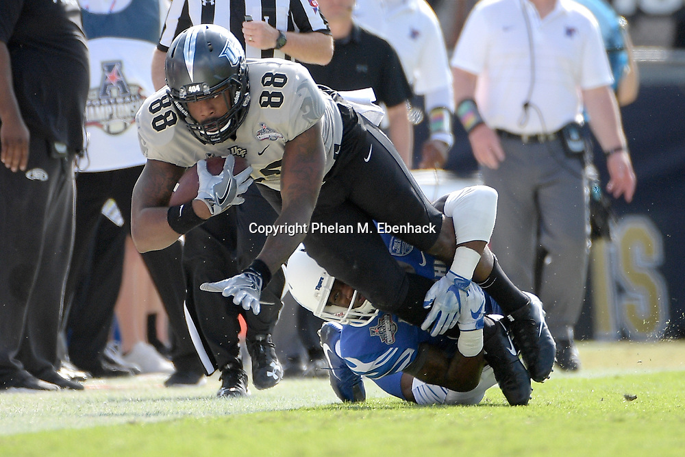 Central Florida tight end Jordan Akins (88) is tackled by Memphis defensive back Josh Perry (4) after catching a pass during the first half of the American Athletic Conference championship NCAA college football game Saturday, Dec. 2, 2017, in Orlando, Fla. (Photo by Phelan M. Ebenhack)