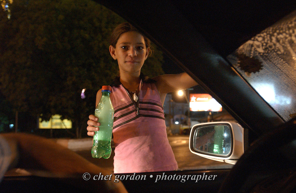 ASUNCION, PARAGUAY.  Young Paraguayan street girl pauses while cleaning a windshield past midnight on Friday, March 17, 2006 in Asuncion, Paraguay. Hundreds of street children, some as young as 4 years old and their parents, work the diesel fumed streets of the capital city by squeegeeing windshields, panhandling and selling various items to drivers.