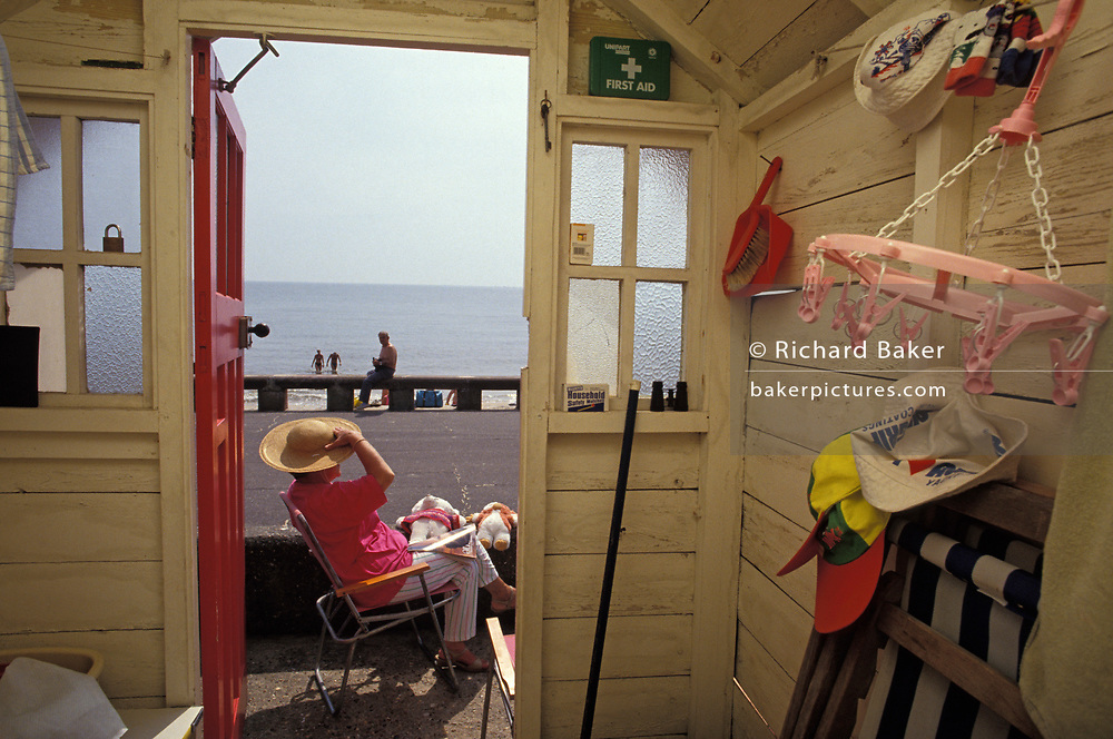 Seen from the inside of her beach hut that looks out to the promenade and sea, a lady enjoys summer sunshine while holding on to her hat while others bathe in the waters beyond, on 12th June 1992, in Lowestoft, England.