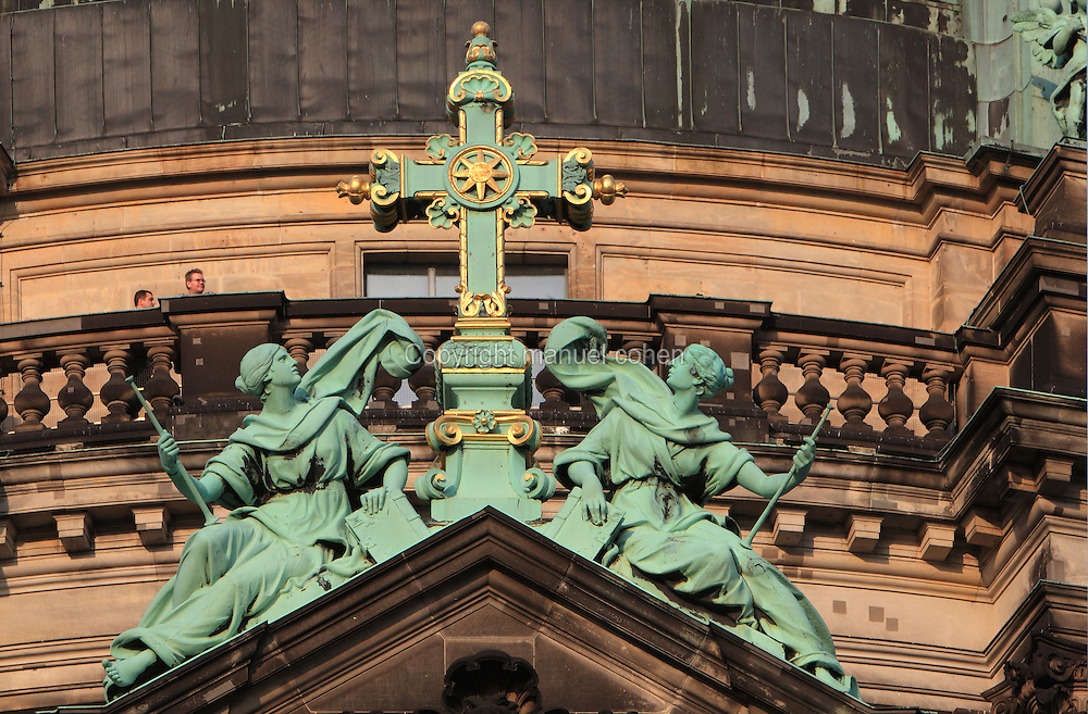 Sculpture on the facade of the Berliner Dom or Berlin Cathedral, redesigned by Julius Raschdorff and completed 1905 in Historicist style after being badly damaged in World War Two, although the original chapel on this site was consecrated in 1454, with tourists on the balcony, Museum Island, Mitte, Berlin, Germany. The buildings on Museum Island were listed as a UNESCO World Heritage Site in 1999. Picture by Manuel Cohen