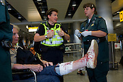 NHS Paramedic Responders attends a lady passenger in Heathrow's terminal 3 who has tripped and badly gashed her leg.