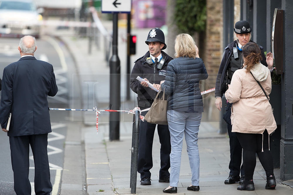 © Licensed to London News Pictures. 17/10/2017. London, UK. Police stand at a cordon around the crime scene. Police are investigating after a man in his 20's was stabbed to death and two others were injured in an incident on Monday night outside Parsons Green underground station a terrorist attack took place last month. Photo credit: Peter Macdiarmid/LNP