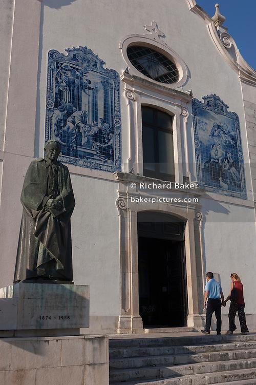 A couple enter the Igreja Paroquial da Vera Cruz (church) for Sunday evening Mass, in Aveiro, Portugal.