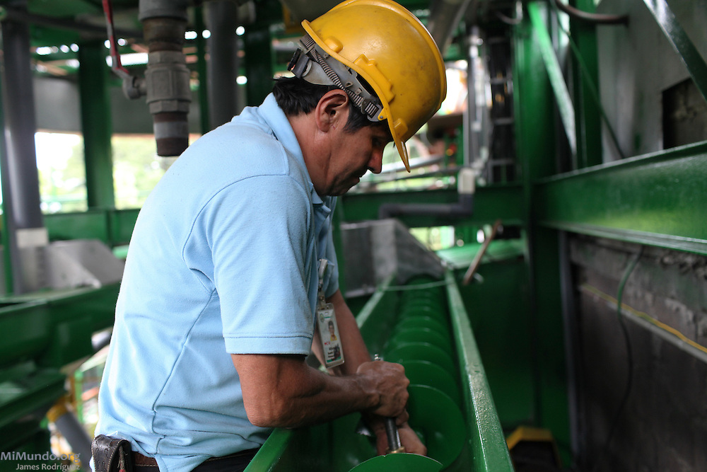 Alfonso Suarez, maintenance engineer for COOPEATENAS, works on a section of the coffee processing plant. COOPEATENAS, Atenas, Alajuela, Costa Rica. August 23, 2012.