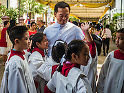 18 SEPTEMBER 2016 - BANGKOK, THAILAND: A priest greets alter servers at Santa Cruz before the church's 100th anniversary mass to start. Santa Cruz Church was establised in 1769 to serve Portuguese soldiers in the employ of King Taksin, who reestablished the Siamese (Thai) empire after the Burmese sacked the ancient Siamese capital of Ayutthaya. The church was one of the first Catholic churches in Bangkok and is one of the most historic Catholic churches in Thailand. The first sanctuary was a simple wood and thatch structure and burned down in the 1800s. The church is in its third sanctuary and was designed in a Renaissance / Neo-Classical style. It was consecrated in September, 1916. The church, located on the Chao Phraya River, serves as a landmark for central Bangkok.       PHOTO BY JACK KURTZ