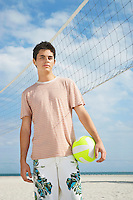 Teenage boy (16-17) standing on beach volleyball court portrait