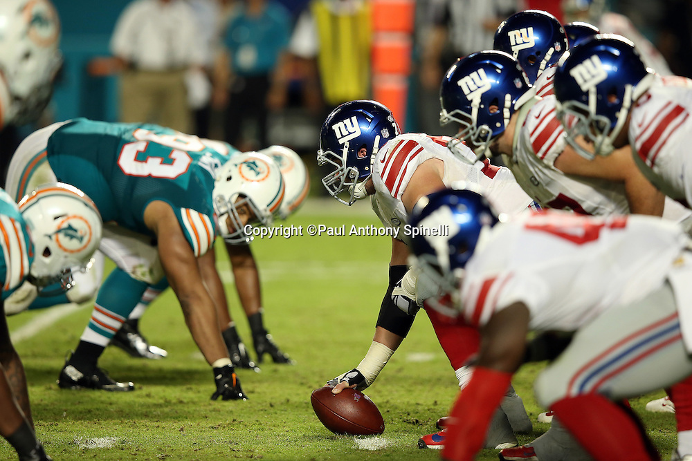 The New York Giants offensive line gets set to snap the ball opposite the Miami Dolphins defensive line during the NFL week 14 regular season football game against the Miami Dolphins on Monday, Dec. 14, 2015 in Miami Gardens, Fla. The Giants won the game 31-24. (©Paul Anthony Spinelli)